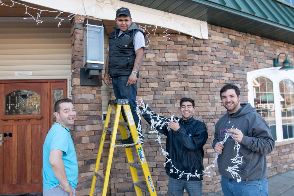 From left, Hector Delgado, Jesus Antonio Montes Hernandez, Jose Delgado and Chris Morales hang Christmas lights above the entrance to Tavern 42 in Plantsville. The four were preparing the tavern for Friday