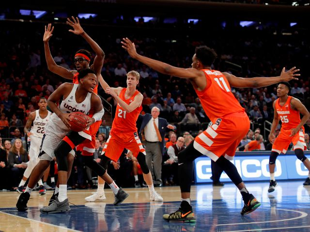 Connecticut forward Josh Carlton (25) drives around Syracuse center Paschal Chukwu (13) during the first half of an NCAA college basketball game, Tuesday, Dec. 5, 2017, in New York. (AP Photo/Julie Jacobson)