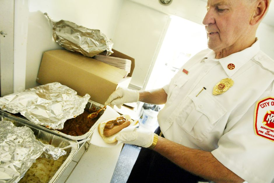 Meriden Fire Marshall Robert Morpurgo prepares a chilli dog during the Brian David Ash Memorial Fire Prevention Fundraiser that is going on in front of the A&P Super Food Mart off the Chamberlain Highway in Meriden through Sunday.