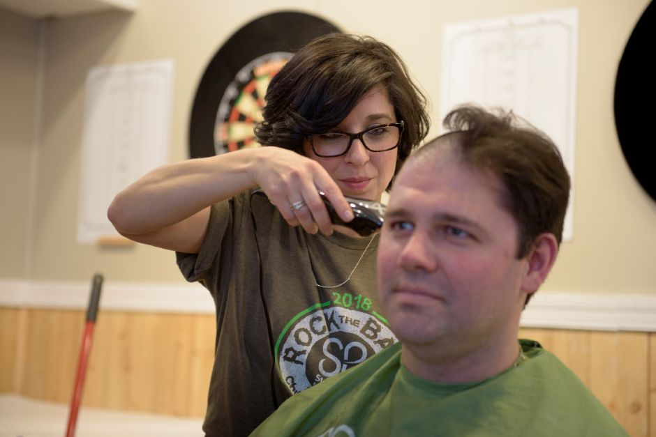 Marinella Oblon of Mari J Salon in Plainville shaves Tom Haggerty's head during the St. Baldrick's fundraiser at Dawg House Bar & Grill in Meriden on Saturday. Photos by Monica Jorge, special to the Record-Journal