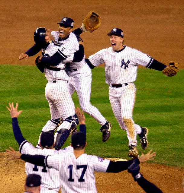 FILE - In this Oct. 27, 1999, file photo, New York Yankees catcher Jorge Posada, left rear, and third baseman Scott Brosius, right rear, rush pitcher Mariano Rivera as teammates run to the mound after the Yankees beat the Atlanta Braves 4-1 in Game 4 of the World Series to sweep the series in New York. Rivera will be inducted into the Baseball Hall of Fame on Sunday, July 21, 2019. (AP Photo/Ron Frehm, File)