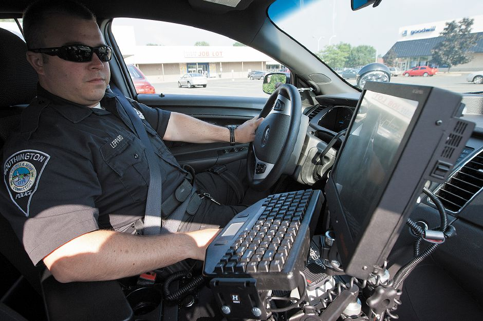 Officer Brian Leppard watches the monitor in his police car that shows the results of the license plate scanning camera
