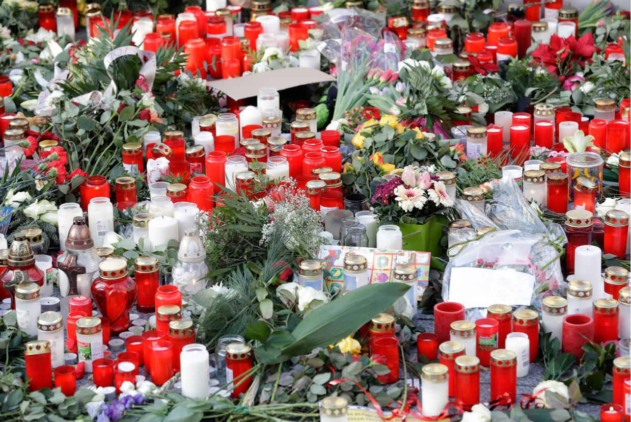 Candles burn between flowers in Berlin, Germany, Wednesday, Dec. 21, 2016, two days after a truck ran into a crowded Christmas market nearby and killed several people. (AP Photo/Michael Sohn)