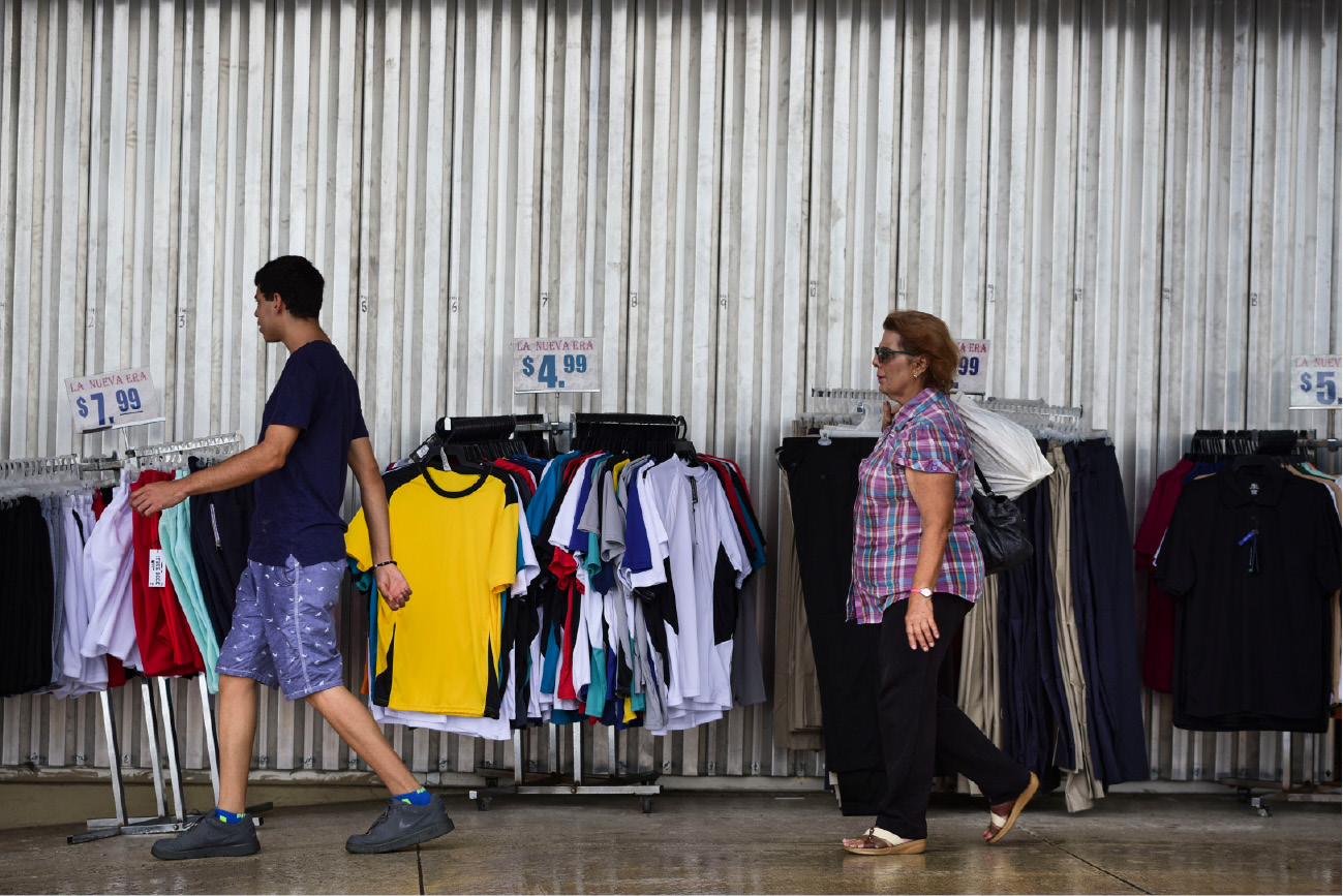 Residents walk past a storefront, paneled with steel sheets in preparation for Hurricane Irma, in Carolina, Puerto Rico, Tuesday, Sept. 5, 2017. Irma grew into a dangerous Category 5 storm, the most powerful seen in the Atlantic in over a decade, and roared toward islands in the northeast Caribbean Tuesday. (AP Photo/Carlos Giusti)