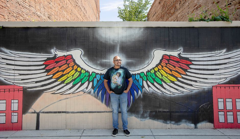 Artist Apollo Maldonado, of Meriden, stands in front of a mural he