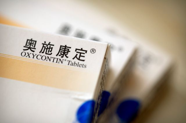 Boxes of OxyContin tablets sold in China sit on a table in southern China