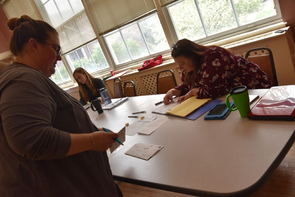 Board of Finance member and volunteer Melissa Kowal (left) reviews absentee votes with official checker Allison Dodge during referendum polling at the Middlefield Community Center, 405 Main St., on Tuesday, May 7, 2019. | Bailey Wright, Town Times