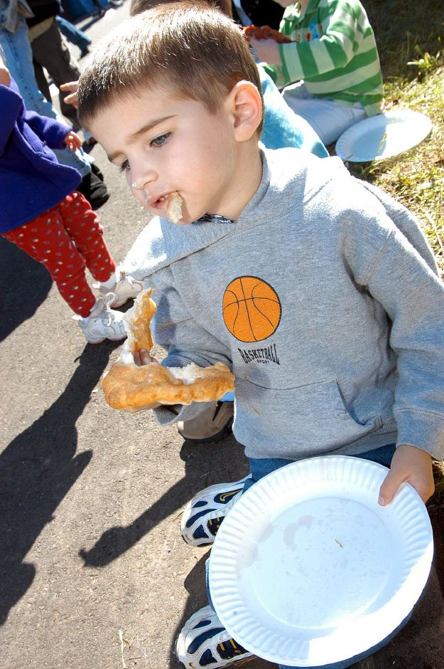 Four-year-old Jared Poulos, of Tolland, chomps on some fried dough at the annual Apple Harvest Festival held Sunday in Southington.