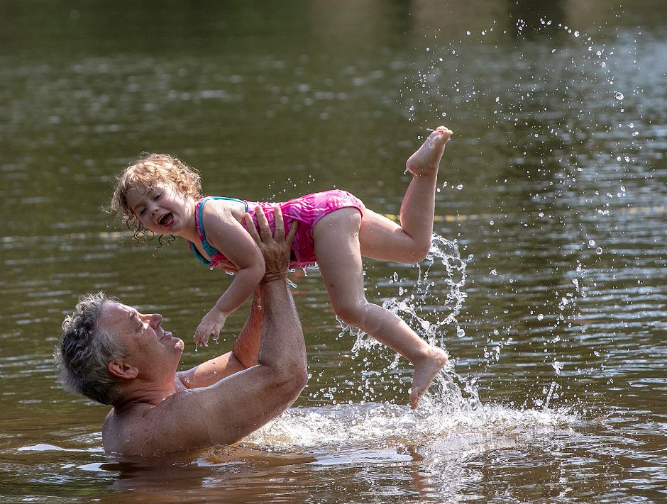 Robert Megna, of New Haven, gives a lift to his 3-year-old daughter, Catherine, while swimming at Wharton Brook State Park in Wallingford on Wednesday. Megna is a former Democratic member of the Connecticut House of Representatives.