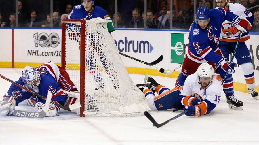 New York Rangers defenseman Steven Kampfer (43) defends as New York Islanders left wing Andrew Ladd (16) tries to get to the puck after falling to the ice in the first period of an NHL hockey game at Madison Square Garden in New York, Wednesday, March 22, 2017. New York Rangers goalie Antti Raanta (32), of Finland, tends the net. (AP Photo/Kathy Willens)