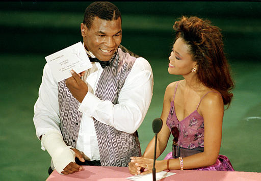 "Heavyweight boxing champion Mike Tyson and his wife, actress Robin Givens, present the Emmy for best costume design for a variety or music program, ""Las Vegas:  An All Star 75th Anniversary Special,"" at the 40th annual Emmy Awards in Pasadena, Ca., Sunday night, Aug. 29, 1988.  Tyson has a cast on his right hand. (AP Photo/Reed Saxon)"