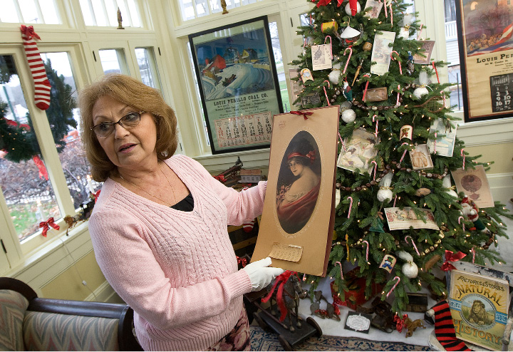 Marie Secondo, curator of the Barnes Museum at 85 N. Main St. in Southington, shows a calendar dating from 1921 as part of the museum's 'Somewhere in Time' exhibit, Wednesday. | Dave Zajac, Record-Journal