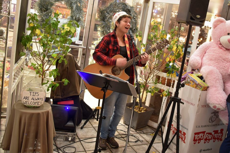 Arlene Wow! performs holiday music for members of the community gathered for a Toys for Tots fundraiser, to donate toys for needy children and enjoy food and drinks at Gaetno