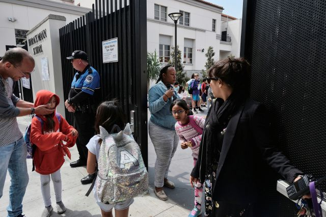 In this Monday May 13, 2019 photo Juliet Fine, right, the principal at Horace Mann School stands and watches as parents pick up their children after a school day in Beverly Hills, Calif. Efforts to combat the problem of school shootings are shifting toward software and other technology to reduce casualties. Beverly Hills officials have added armed security guards, surveillance cameras and an app to report attacks and connect with police. (AP Photo/Richard Vogel)