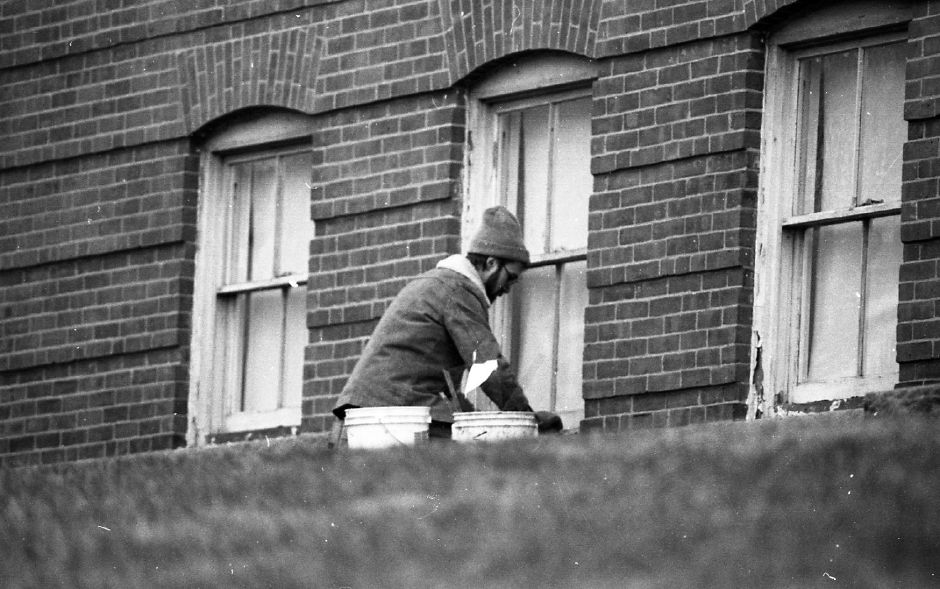 RJ file photo - Glazier Shawn Hopins repairs windows at Heritage Christian Academy in Wallingford recently. Hopkins, who works for Andrade Glass in Wallingford, said he was thankful the windows that were broken were on ground level, Jan. 2, 1989.