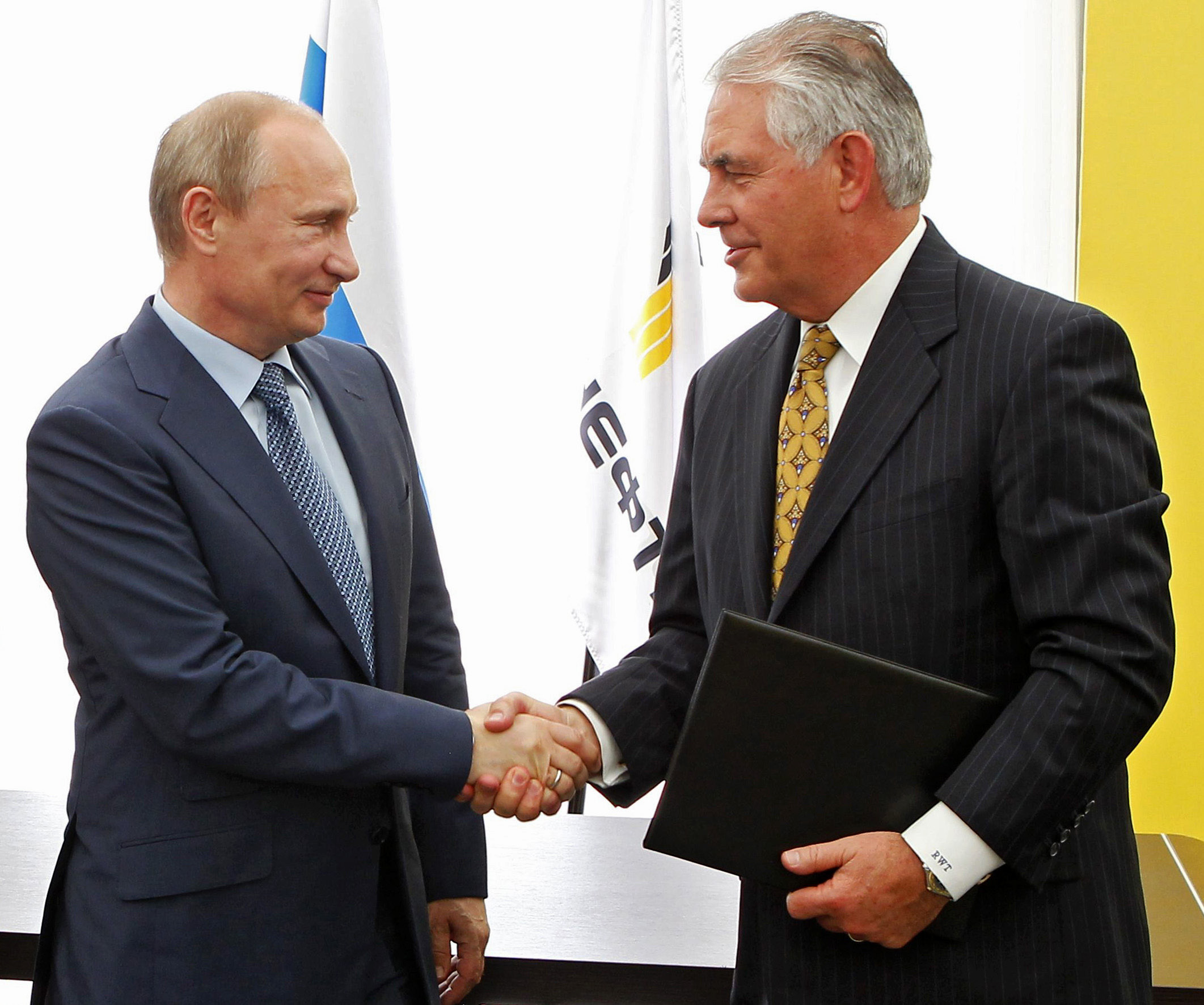 FILE- In this June 15, 2012, file photo, Russian President Vladimir Putin, left, and ExxonMobil CEO Rex Tillerson shake hands at a signing ceremony of an agreement between state-controlled Russian oil company Rosneft and ExxonMobil at the Black Sea port of Tuapse, southern Russia. President-elect Donald Trump selected Tillerson to lead the State Department on Monday, Dec. 12, 2016. (Mikhail Klimentyev/RIA-Novosti, Presidential Press Service via AP, Pool, File)