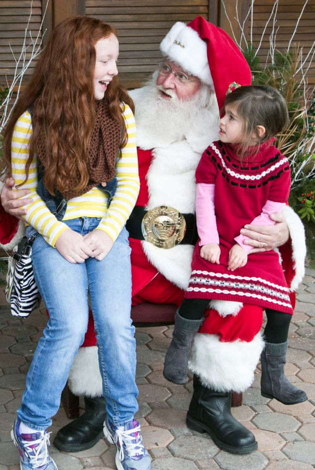 File photo – Emma Foley, 11, left, of Missouri, and Mila Rossi, 3, right, of Meriden, sit on Santa Claus