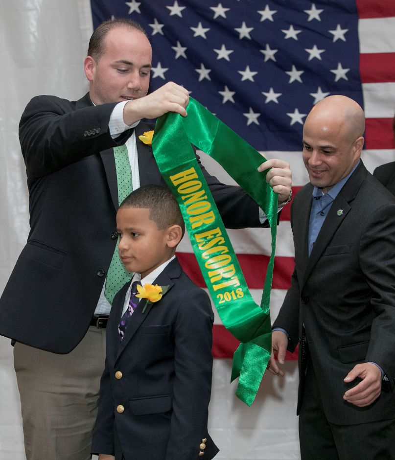 Malachi Felton, 6, of Meriden, receives his honor escort sash from Mayor Kevin Scarpati, left, and city councilor Miguel Castro during the annual Little Miss Daffodil event at Hubbard Park in Meriden, Wednesday, April 25, 2018. Malachi is a student at Our Lady of Mount Carmel School. Dave Zajac, Record-Journal