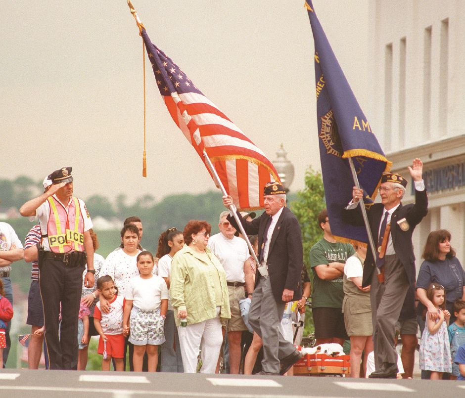 RJ file photo -Wallingford Police Lt. Pete Cameron salutes the colors carried by members of the American Legion Post 73, May 25, 1998.