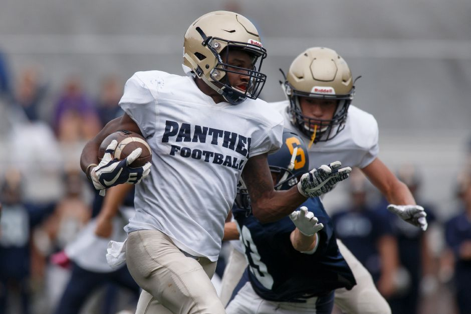 Tremayne Carter returns a kick 80 yards for a touchdown during Friday's preseason scrimmage with Simsbury at Falcon Field. | Justin Weekes / Special to the Record-Journal