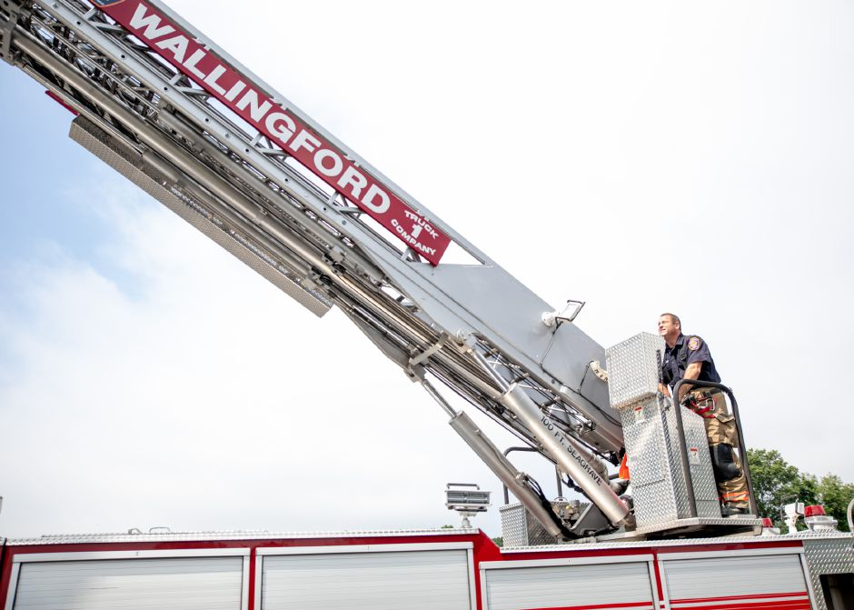 Wallingford Firefighter David Gale raises the ladder on Engine 1 to get a bird