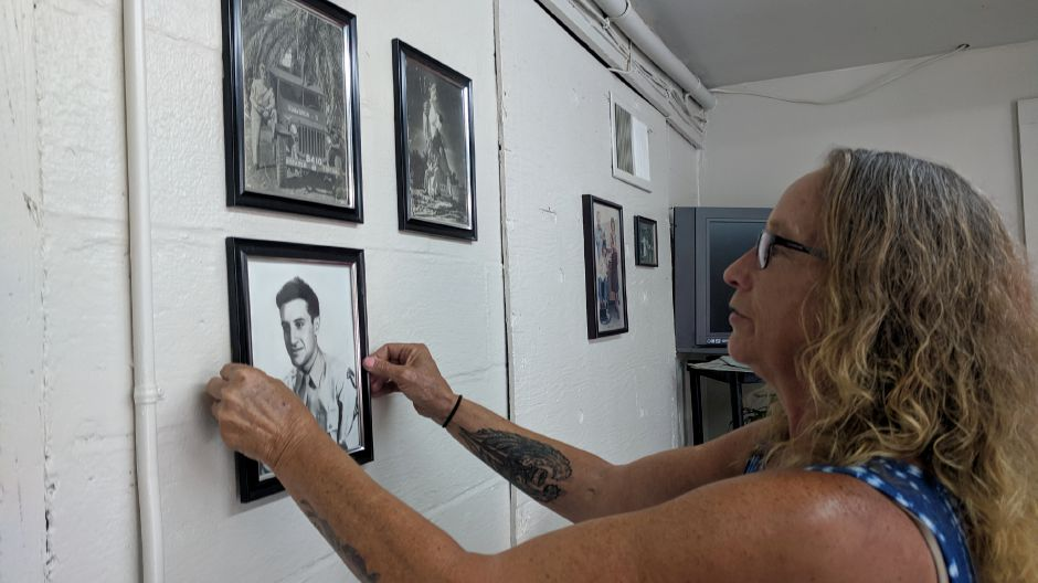 Maria Mazzacane Perez hangs a framed photo of her father, Joseph Mazzacone, on one of the walls at Cheshire Barber Shop. Mazzacane Perez reopened the shop this week, after it had been closed for more than two months. | Michael Gagne, Record-Journal