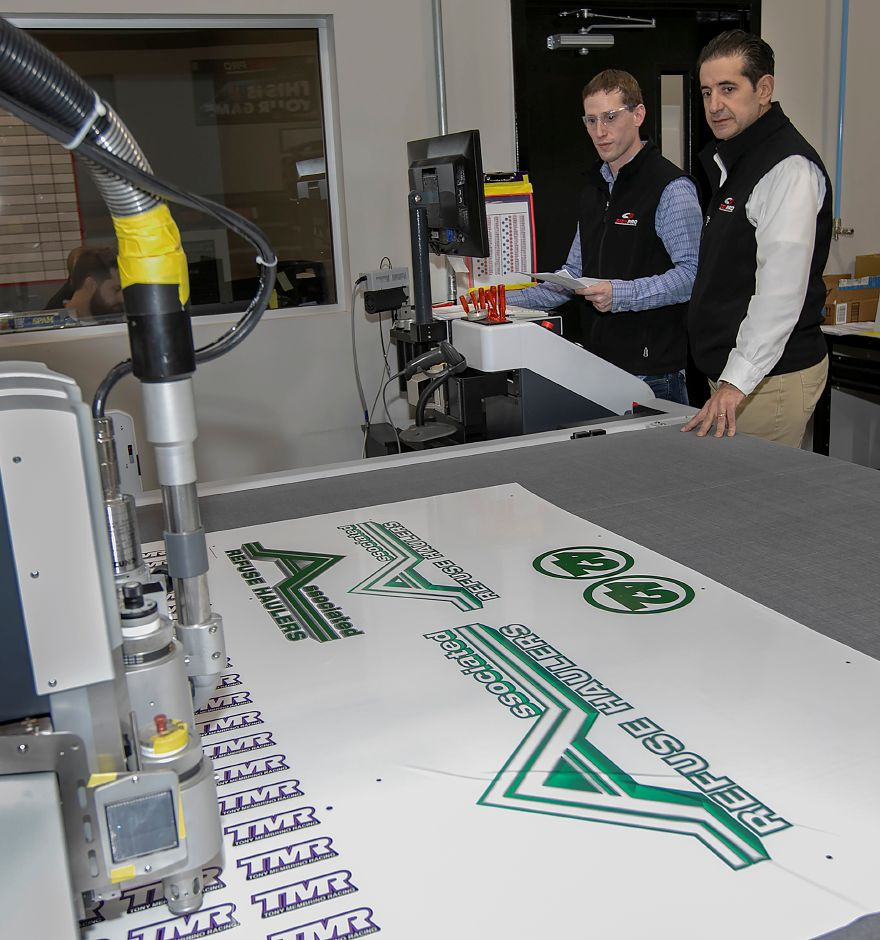 Owner Peter Rappoccio, right, and William Arcari, lead graphics coordinator, watch over a machine Wednesday as it creates a sign for a customer at Sign Pro in Southington.Dave Zajac, Record-Journal