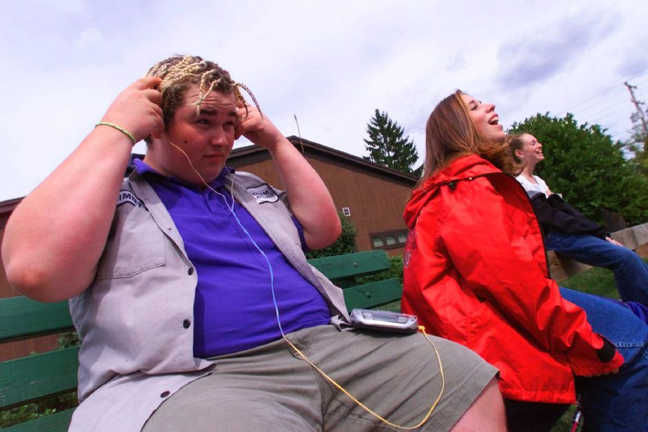 Listening to Pink Floyd, sophomore James Hryb ,16 adjusts his headphones while waiting for family to pick him up outside Cheshire High School after the first day of classes Monday for freshmen and sophomores Aug. 30, 2019 . Next to him are sophomores Holly DiLauro ,16 (center) and Heather Zello,15.