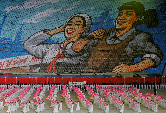 "In this Tuesday, July 16, 2019, photo, North Koreans hold cards to make an image depicting a worker and a farmer during a mass game performance of ""The Land of the People"" at the May Day Stadium in Pyongyang, North Korea. (AP Photo/Vincent Yu)"