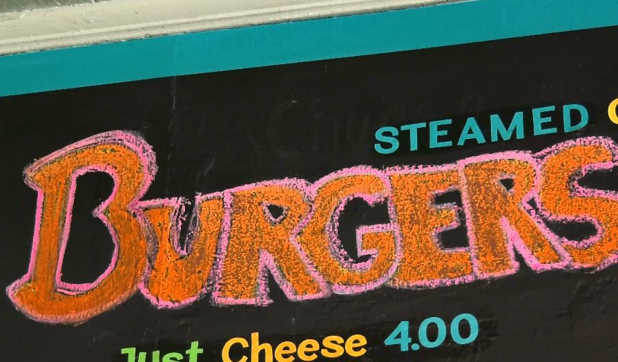 A chalkboard sign for popular steamed burgers at Sara J