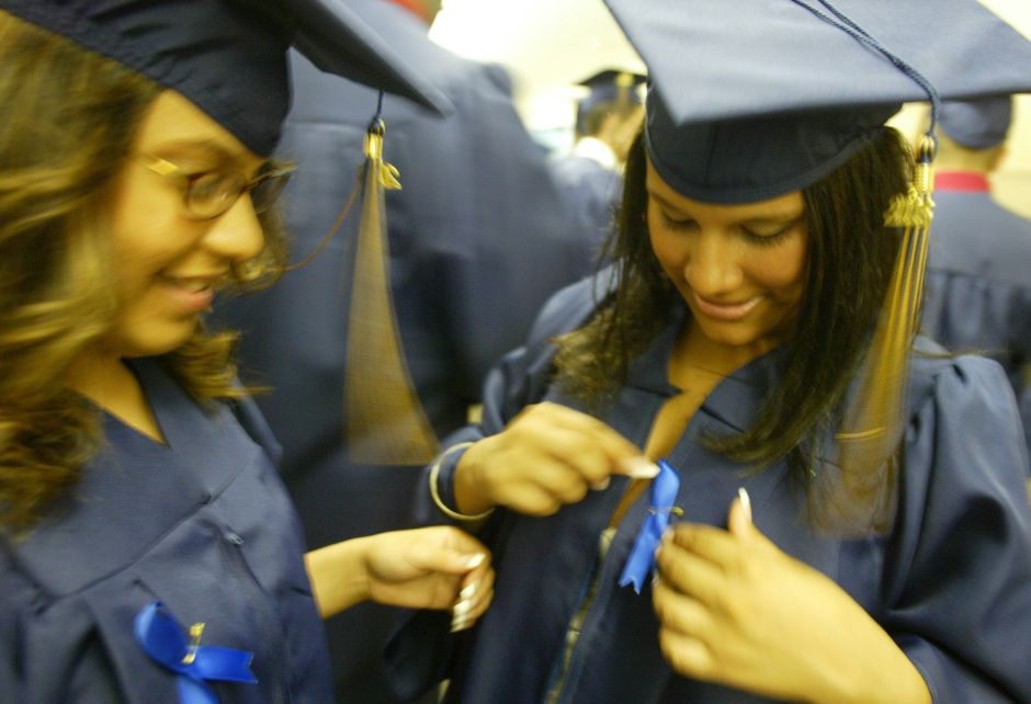 Chrissy Cruz, 17, right, attaches a ribbon to her robe in memory of Fredi (cq) Castillo before commencement ceremonies at Platt High School June 20, 2006. Castillo died in a biking accident recently and was to be the first to graduate in the class of 2006. At left is friend Yanise(cq) Gonzalez, 18,.