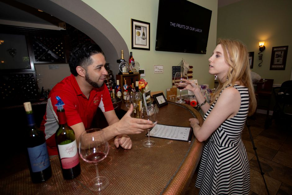 Paradise Hill Vineyards Bartender Mario Mena explains the finers points of the vineyards wines with Record-Journal Digital Content Producer Ashley Kus May 24, 2018. | Richie Rathsack, Record-Journal