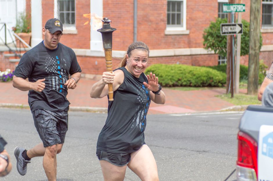 An officer carries the torch down South Main Street in Cheshire as part of the Law Enforcement Torch Run for Special Olympics Connecticut on June, 8 2018 | Andrew Baxter, Special to the Record-Journal