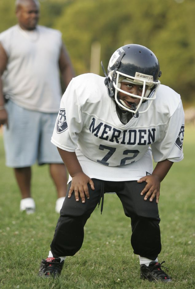 "Meriden Raider Isaiah Davis, 8, stands at the ready bearing the number of popular defensive lineman William ""The Refrigerator"" Perry who played for Chicago in the 80"