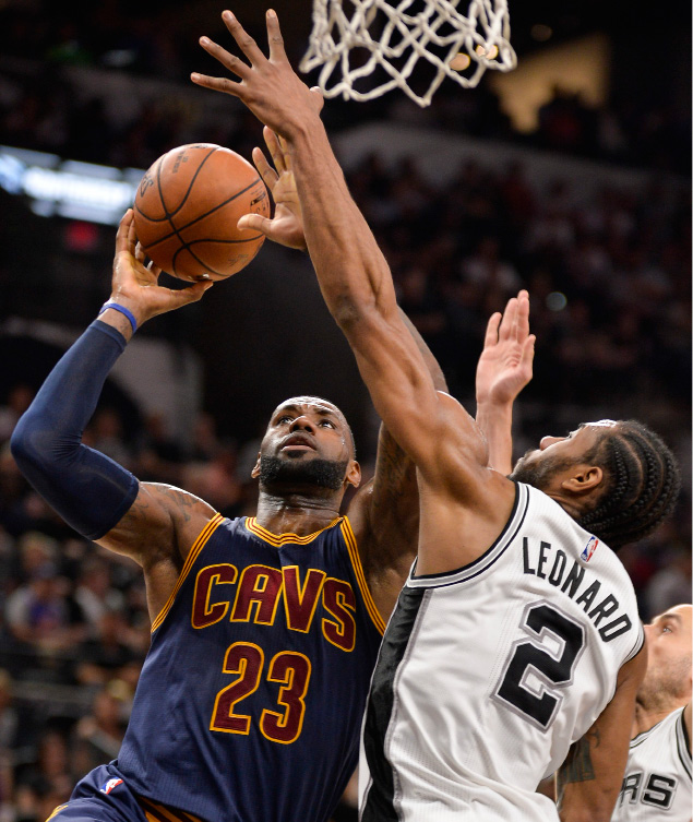 Cleveland Cavaliers forward LeBron James (23) shoots against San Antonio Spurs forward Kawhi Leonard during the first half of an NBA basketball game, Monday, March 27, 2017, in San Antonio. (AP Photo/Darren Abate)