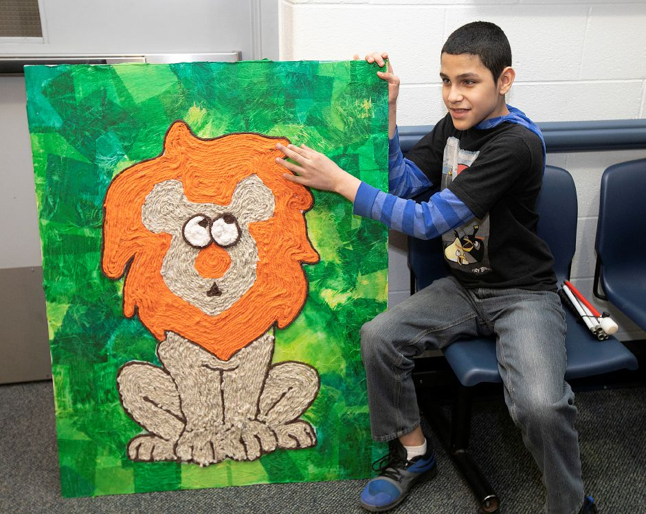 Sixth-grade student Jose Nieves Roman, 12, who is blind, feels around his art project of a lion made from mixed media at Lincoln Middle School in Meriden, Tues., Jan. 8, 2019. Roman used yarn of different textures in creating the project over a two-month period. Dave Zajac, Record-Journal