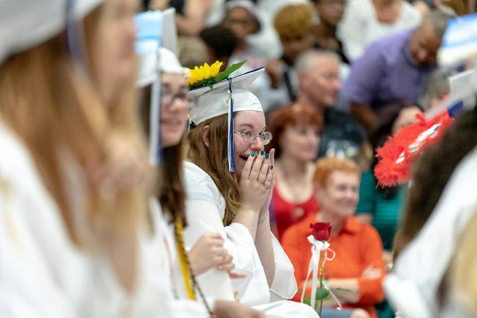 A student laughs during the Plainville High School 2019 graduation ceremony, held in the school