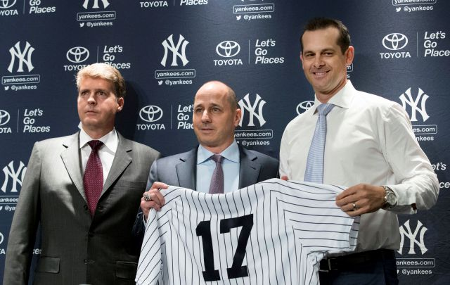 New York Yankees owner Hal Steinbrenner, left, general manager Brian Cashman, center, and Aaron Boone, pose for photographers during a news conference introducing  Boone as the baseball team