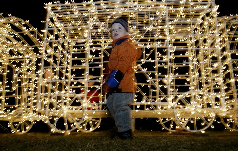 Garrett Prushinski age 3 of Southington makes his past a Christmas lights decorated locomotive while attending Christmas in the Park celebration at Hubbard Park on Tuesday evening.