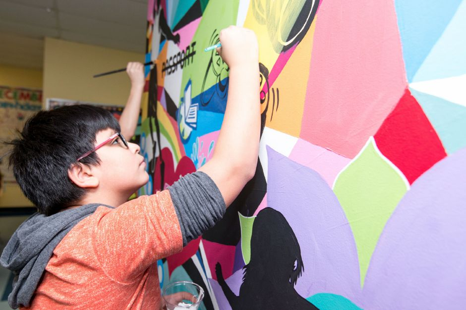 Sebastian Pinos, 12, sharpens up the outline of a game controller in a mural being painted at the Ulbrich Boy