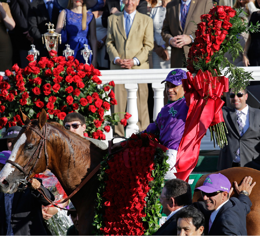 Victor Espinoza celebrates after riding California Chrome to a victory during the 140th running of the Kentucky Derby horse race at Churchill Downs Saturday, May 3, 2014, in Louisville, Ky. (AP Photo/David J. Phillip)