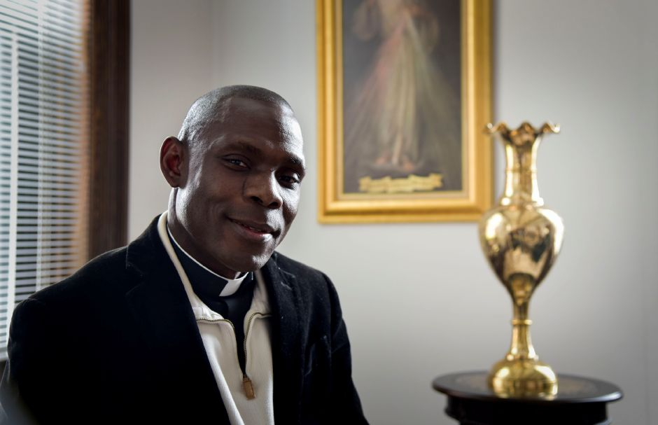 Rev. Kingsley Ihejirika poses in his office at Most Holy Trinity Church in Wallingford on April 25, 2018. Ihejirika is raising money to build a medical clinic in his hometown of Obike, Nigeria. | Matthew Zabierek, Record-Journal