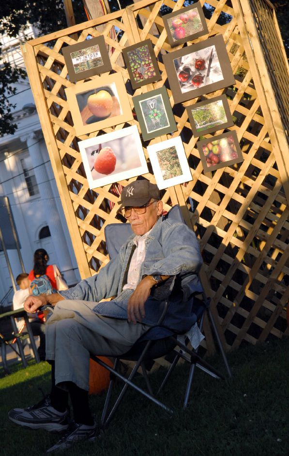 SOUTHINGTON, Connecticut - Friday, September 28, 2007 - Sitting in front of images of apples on Friday, Joe Bouchard of Southington watches the opening ceremonies of the Apple Harvest Festival on Main Street. Rob Beecher / Record-Journal