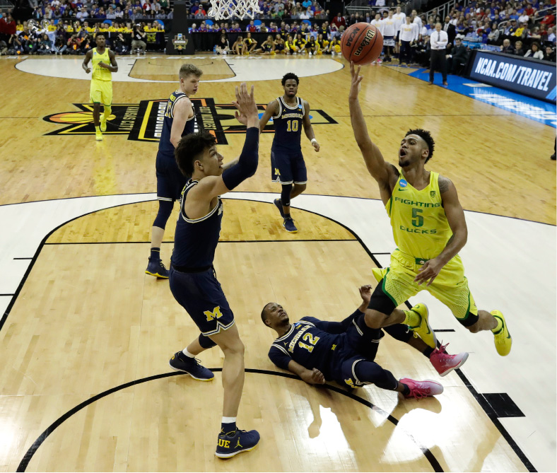 Oregon guard Tyler Dorsey (5) drives to the basket over Michigan