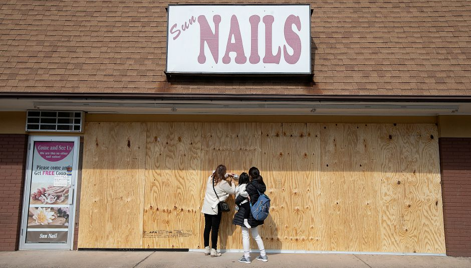 Jenny Rhee, left, owner of Sun Nails Salon, and a relative, who declined to be identified, post a sign to the boarded up business at 826 E. Center St., Wallingford, Thurs., Mar. 14, 2019. A vehicle crashed into the nail salon Thursday morning, significantly damaging the storefront. Dave Zajac, Record-Journal