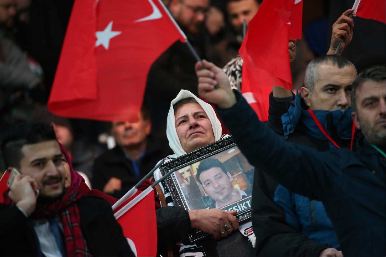 A relative of a victim of an attack, holding picture of her loved one, stands prior to what the organisers said was a soccer match between Turkey