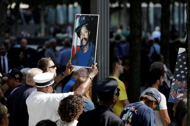A photograph of fallen firefighter Leon Smith, Jr. is held up during a ceremony marking the 18th anniversary of the attacks of Sept. 11, 2001 at the National September 11 Memorial, Wednesday, Sept. 11, 2019 in New York. (AP Photo/Mark Lennihan)