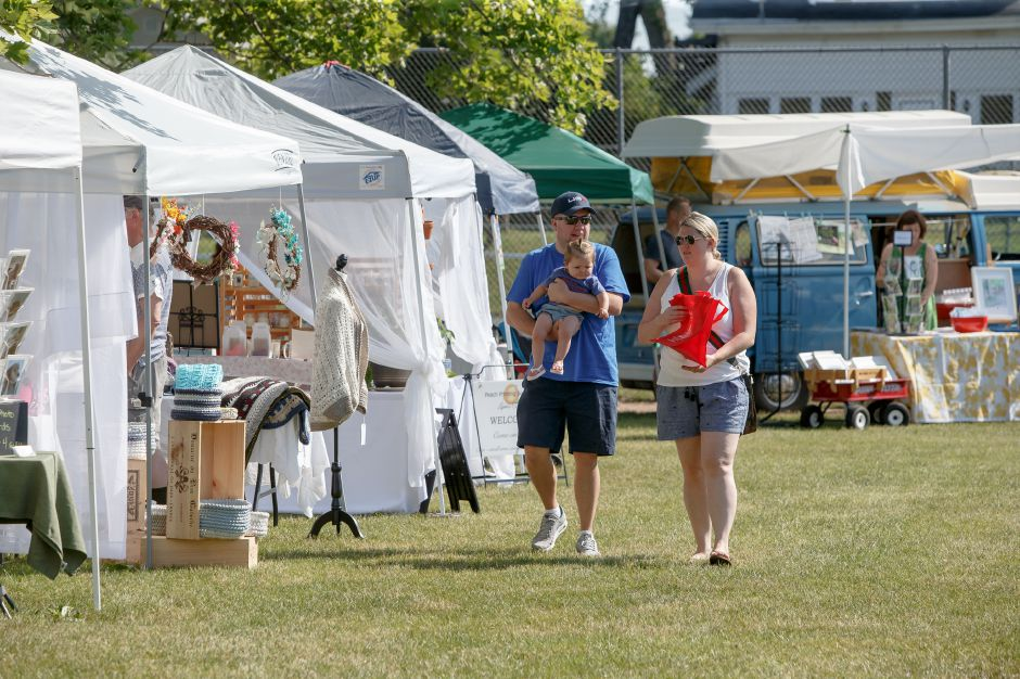 The Breuler family Derek, Courtney and 4 month old CHarlotte of Wallingford walk the booths Saturday during opening weekend of the Wallingford Garden Market at Doolittle Park in Wallingford June 30, 2018 | Justin Weekes / Special to the Record-Journal