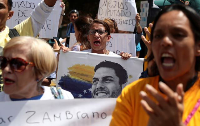 A woman holds an image of jailed opposition lawmaker and outspoken critic of President Nicolas Maduro, Juan Requesens, as she chants with others in support of the opposition controlled National Assembly, in Caracas, Venezuela, Thursday, May 16, 2019. Diplomatic efforts aimed at resolving Venezuela