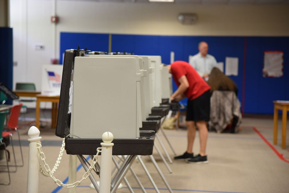 A resident places his vote at the former Korn School building, where voting on Regional School District 13